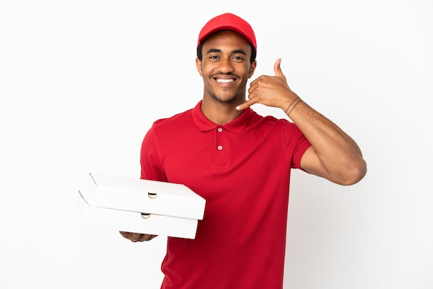 Un livreur de pizzas afro-américaines ramassant des boîtes de pizza sur un mur blanc isolé faisant un geste téléphonique. rappelle-moi signe