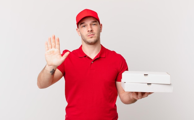 Livreur de pizzas à l'air sérieux, sévère, mécontent et en colère montrant la paume ouverte faisant un geste d'arrêt