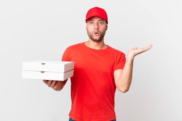 Livreur de pizzas à l'air surpris et choqué, avec la mâchoire baissée tenant un objet