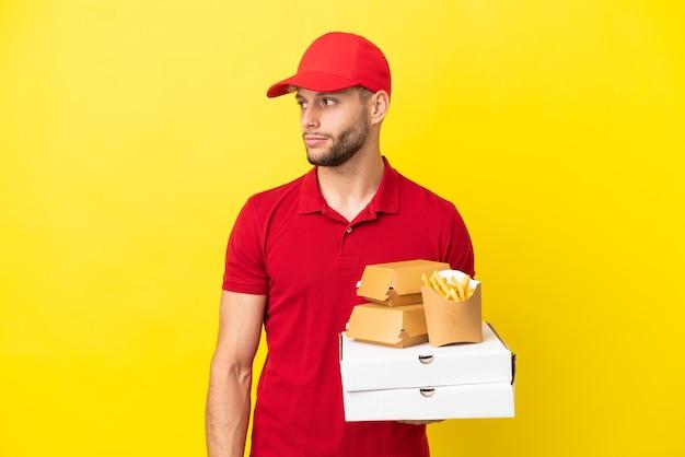 Livreur de pizzas ramasser des boîtes de pizza et des hamburgers sur fond isolé regardant sur le côté