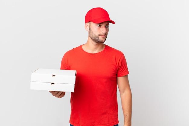 Livreur de pizzas se sentant triste, contrarié ou en colère et regardant sur le côté