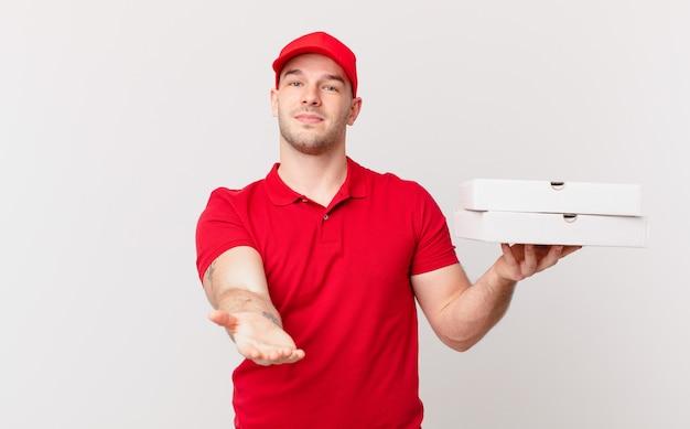 Livreur de pizzas souriant joyeusement avec un regard amical, confiant et positif, offrant et montrant un objet ou un concept