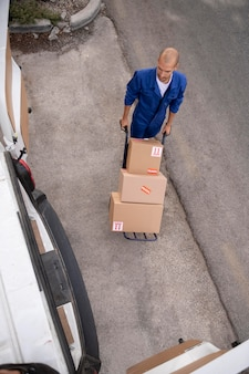 Livreur plein coup transportant des boîtes