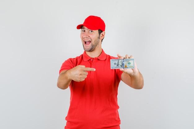 Livreur Pointant Sur Billet De Dollar En T-shirt Rouge Photo gratuit