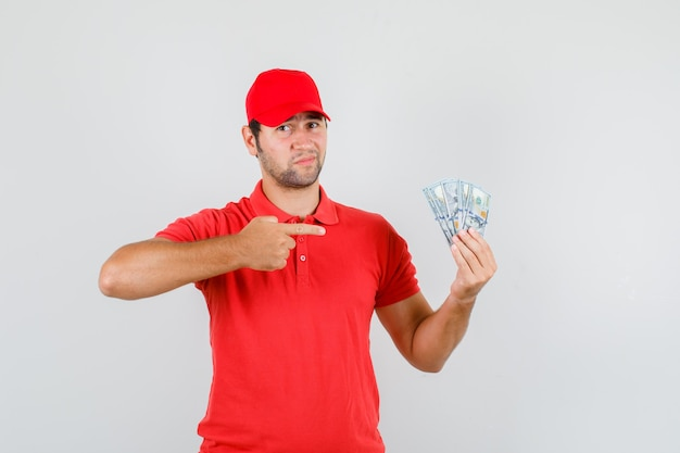 Livreur pointant sur les billets en dollars en t-shirt rouge