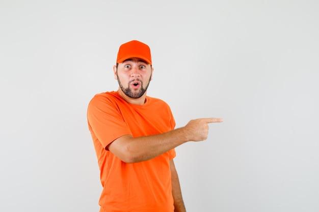 Livreur pointant sur le côté en t-shirt orange, casquette et l'air étonné, vue de face.
