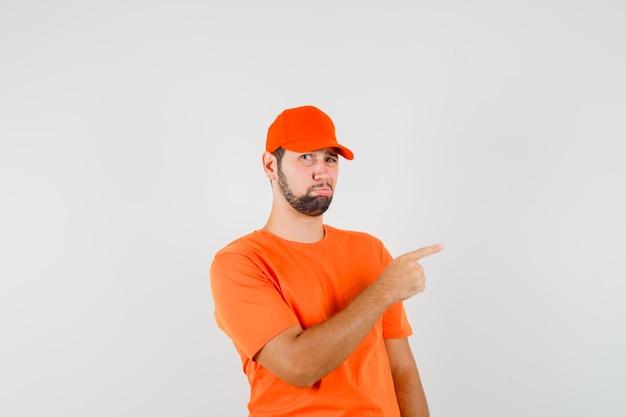 Livreur pointant sur le côté en t-shirt orange, casquette et l'air offensé, vue de face.