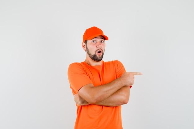 Livreur pointant sur le côté en t-shirt orange, casquette et l'air surpris. vue de face.