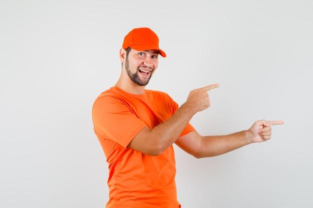 Livreur pointant sur le côté en t-shirt orange, casquette et semblant joyeux. vue de face.