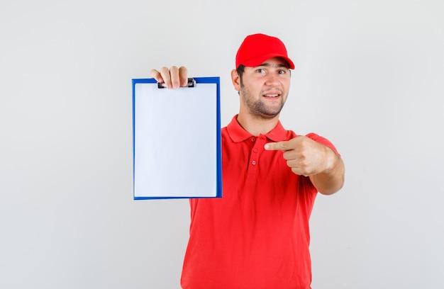 Livreur pointant sur le presse-papiers en t-shirt rouge