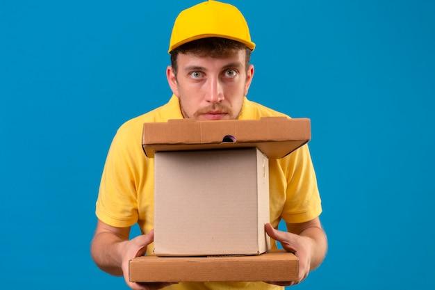 Livreur en polo jaune et casquette à la fatigue et l'ennui tenant des boîtes en carton sur bleu isolé