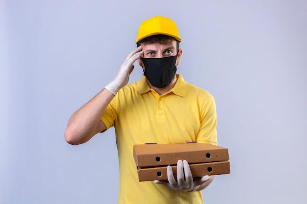 Livreur en polo jaune et casquette portant un masque de protection noir tenant des boîtes de pizza à la tête malade fatiguée et onworked ayant mal à la tête debout sur blanc isolé