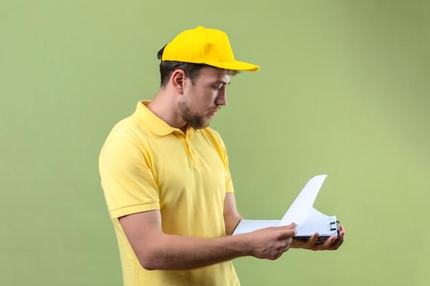 Livreur en polo jaune et casquette à la recherche de blancs dans sa main avec un visage sérieux debout sur vert isolé