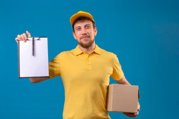 Livreur en polo jaune et casquette tenant une boîte en carton montrant le presse-papiers avec des blancs smiling friendly sur bleu