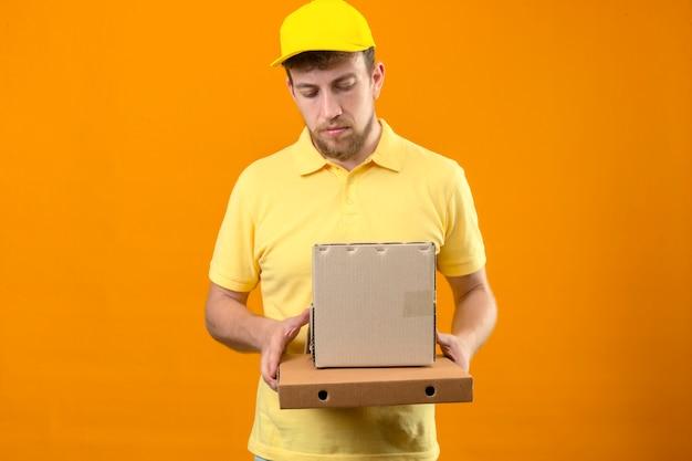 Livreur en polo jaune et casquette tenant des boîtes en carton à la triste avec visage malheureux debout sur orange isolé