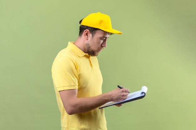 Livreur en polo jaune et casquette tenant le presse-papiers avec des blancs d'écrire quelque chose avec un visage sérieux debout sur le vert
