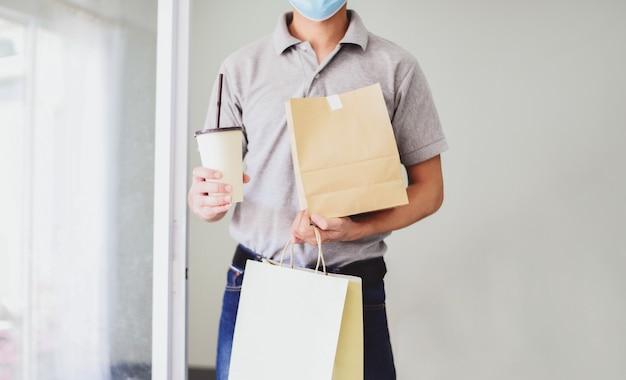 Livreur portant un masque facial et main tenant la livraison de nourriture service d'emballage alimentaire à domicile