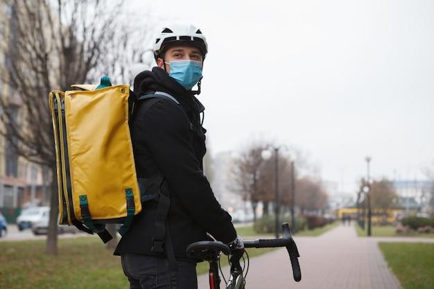 Livreur portant un masque médical et un sac à dos thermo, regardant par-dessus son épaule en marchant avec son vélo
