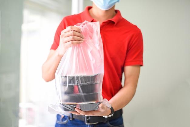 Livreur portant un masque protecteur contre le coronavirus et main tenant une boîte de nourriture d'emballage alimentaire