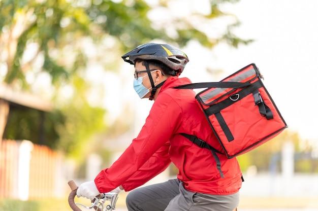 Livreur portant un masque de protection pour éviter le virus corona uniforme rouge cyclisme pour livrer des produits aux clients à la maison.