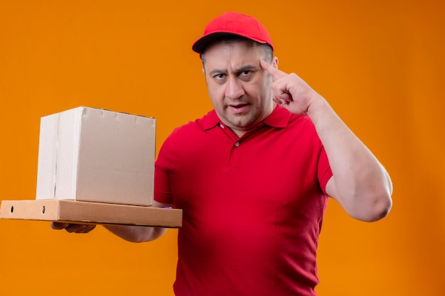 Livreur portant un uniforme rouge et cap tenant des boîtes en carton pointant le temple avec le doigt se concentrant dur sur une idée debout