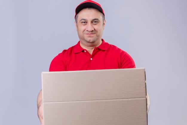 Livreur portant un uniforme rouge et une casquette tenant une boîte en carton à la recherche de sourire confiant debout sur un espace blanc isolé