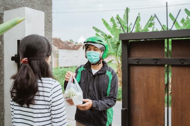 Livreur porter un masque facial lors de la livraison de nourriture
