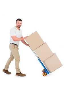 Livreur en poussant le chariot des boîtes sur fond blanc