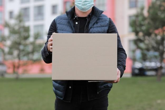 Livreur recadrée en bonnet rouge, masque médical pour le visage tenir une boîte en carton vide à l'extérieur