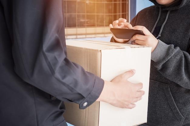Le livreur reçoit le colis de la boîte à colis sur le smartphone de l'application de signature du client asiatique pour recevoir les colis en carton de la livraison, en signant le reçu. expédition d'achats en ligne, concept de service de livraison de commerce électronique
