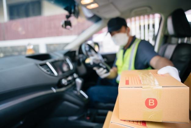 Un livreur récupère une boîte dans la voiture d'un ami pour la livrer à un client, select focus a box.