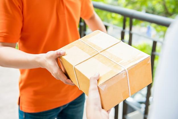 Livreur remettant une boîte à colis à un client