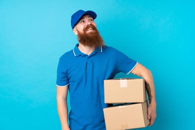 Livreur rousse sur mur bleu isolé en levant tout en souriant
