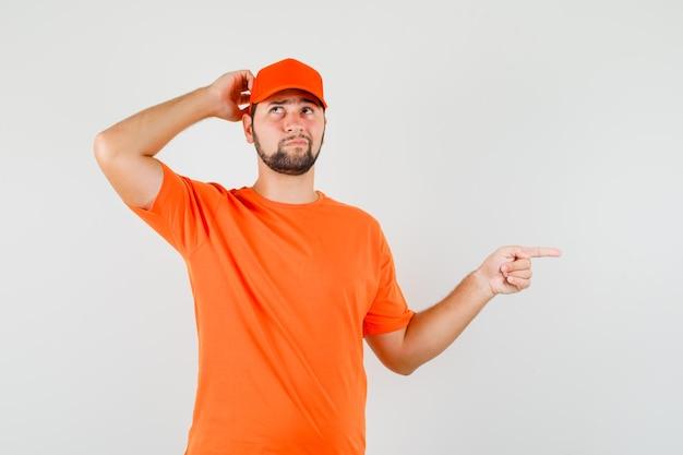 Livreur se grattant la tête, pointant vers le côté en t-shirt orange, casquette et l'air pensif. vue de face.