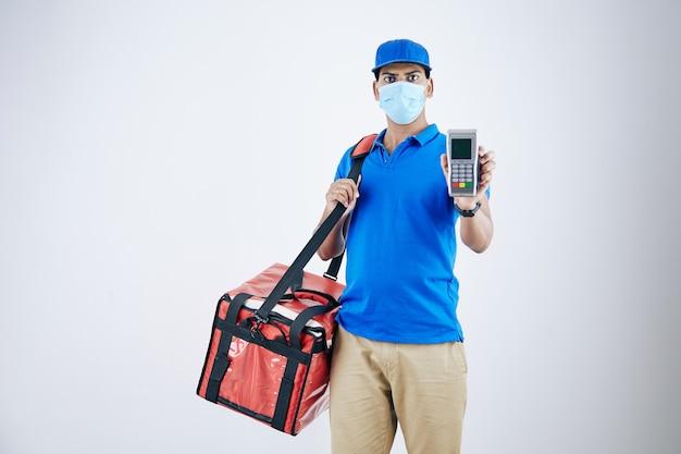 Livreur sérieux et confiant dans un masque médical tenant un sac isotherme montrant un terminal de paiement