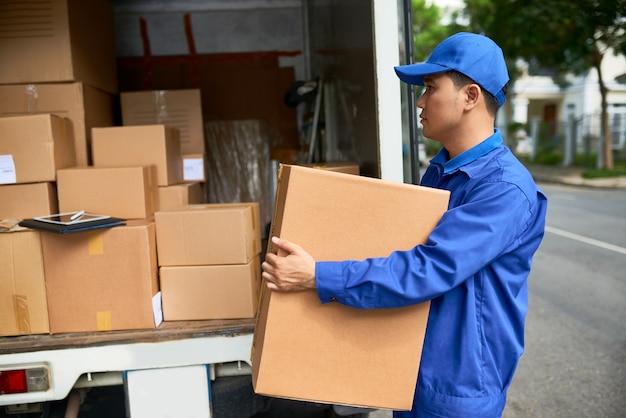 Livreur sérieux en uniforme bleu et camion de chargement de cap avec des boîtes cardbord