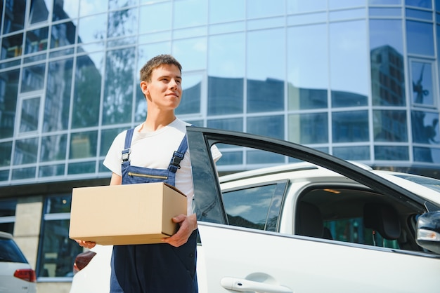 Livreur souriant debout devant sa voiture