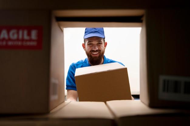 Livreur souriant à plan moyen avec des boîtes