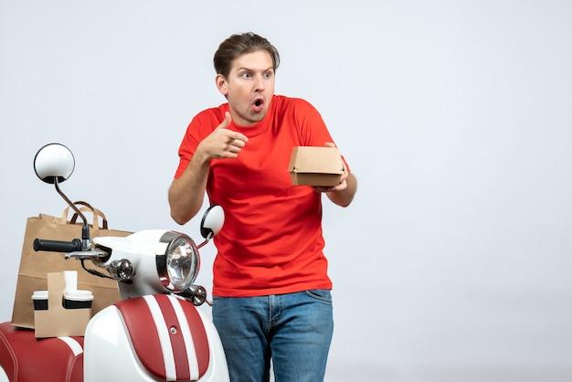 Livreur surpris et émotionnel en uniforme rouge debout près de scooter tenant une petite boîte sur fond blanc