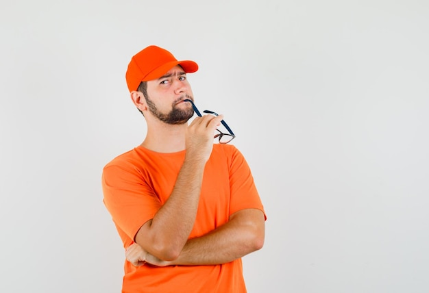 Livreur en t-shirt orange, casquette mordant des lunettes et semblant irrésolu, vue de face.