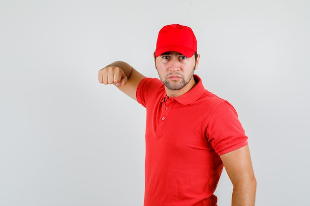Livreur en t-shirt rouge, casquette menaçant avec le poing et à la fureur