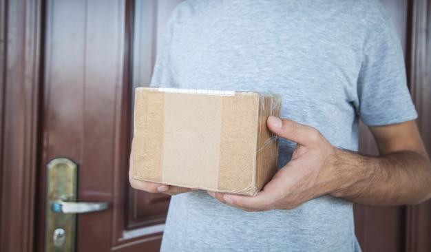 Livreur tenant la boîte à colis.