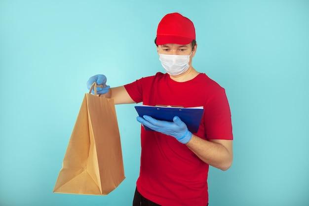 Livreur tenant des boîtes en carton dans des gants en caoutchouc médical et un masque