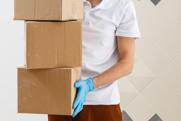 Livreur tenant des boîtes en carton dans des gants et un masque en caoutchouc médical. espace de copie. transport de livraison rapide et gratuit. achats en ligne et livraison express. quarantaine