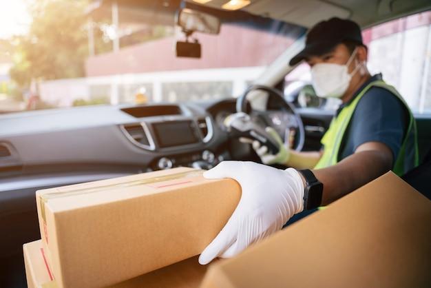 Un livreur tenant un lecteur de carte de crédit récupère une boîte dans la voiture d'un ami pour la livrer à un client, select focus a box.