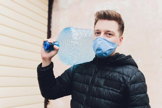 Livreur tenant la livraison d'eau dans des gants et un masque en caoutchouc médical. copier l'espace. transport de livraison rapide et gratuit. achats en ligne et livraison express. quarantaine.