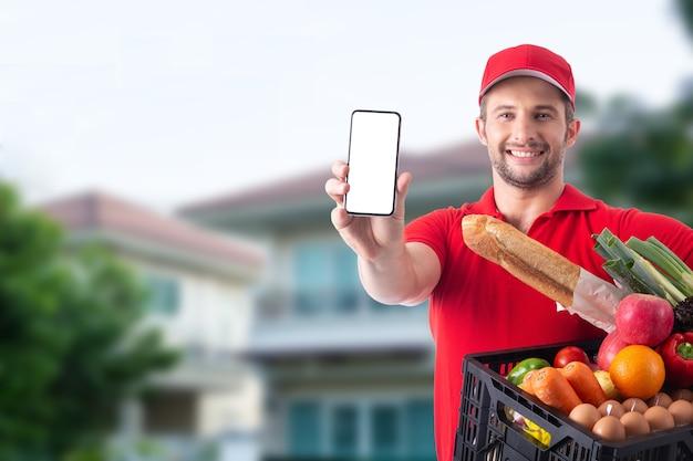 Livreur tenant de la nourriture et montre un téléphone portable pour le client
