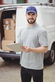 Livreur tenant le presse-papiers devant sa camionnette