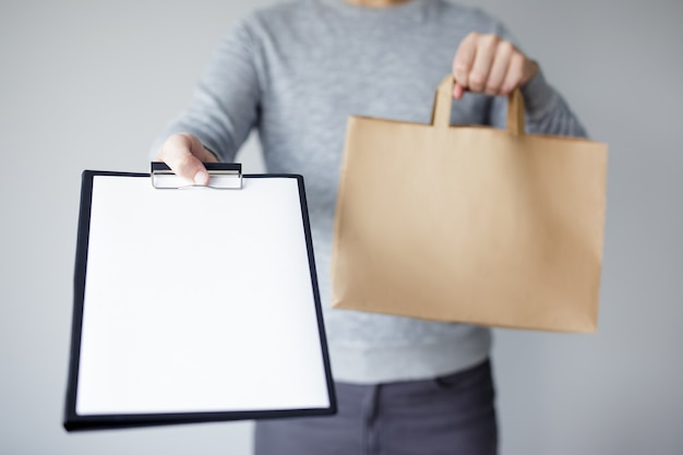 Livreur tenant un sac en papier et montrant le presse-papiers avec du papier de facture vierge - espace de copie