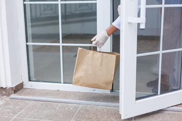 Livreur tenant un sac en papier avec de la nourriture sur l'entrée blanche du fond de la maison, livreur de nourriture dans un masque de protection